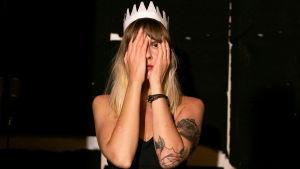 Nuori vaaleahiuksinen nainen paperikruunu päässään kädet kasvoilla niin, että vaan toinen silmä ja vähän kasvoista näkyy.n