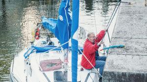 Purjevene odottaa kanavassa, punatakkinen mies istuu veneenkannella ja pitää kiinni kanavanlaituriin kiinnitetystä köydestä.