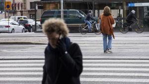 Nainen puhuu puelimessa ja ylittää tietä etualalla. Takana toinen nainen ja kaksi pyöräilijää.