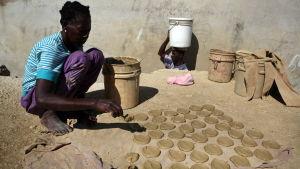 En kvinna i Cité Soleil bakar kakor med lera, olja och salt för att dämpa hungern.