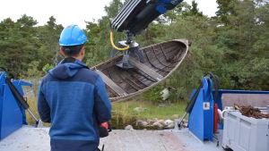 Lyftkran lyfter en gammal båt.