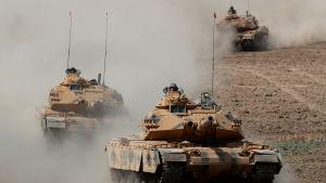 Tre turkiska stridsvagnar kör i ett löst led mot kameran.