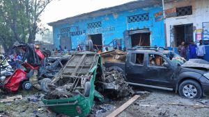 Människor står och ser på den förödelse som de två bilbomberna orsakade utanför hotellet i Mogadishu.