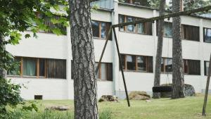 En gunga och gräsmatta framför ett vitt höghus.