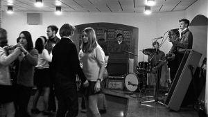 Unga människor dansar och en orkester spelar på 60-talet