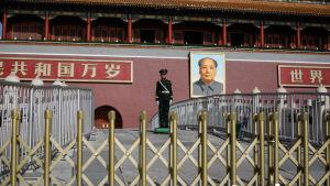 En polis står framför ett porträtt av Mao vid ingången till den förbjudna staden i Peking.