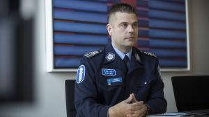 En medelåldersman i polisuniform sitter vid ett bord med knäppta händer.