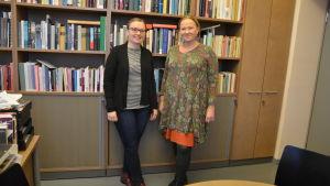 två kvinnnor står framför en bokhylla