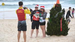 Julfirare poserar på Bondi Beach i Sydney, Australien.