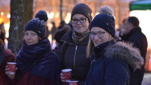 Tre unga kvinnor följer med ljusshowen då Åbo Akademi 100 år- jublieumsåret invigdes.