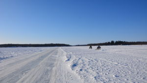 Två snöskotrar på isen utanför Gerby i Vasa.