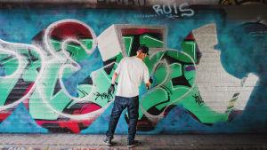Janne Saarikoski gör graffitikonst. En färggrann vägg där det står hans graffitialias DESI.