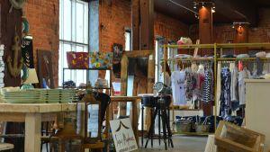 Bord med föremål och klädhängare med klädesplagg inne i en byggnad i tegel med stora fönster.