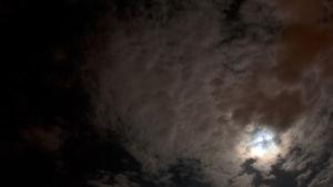 en mörk natthimmel med moln och strimmor av månljus.