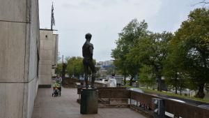 Wäinö Aaltonens museum utifrån, en staty av en man står i förgrunden, en kvinna skuffar en barnvagn i bakgrunden.