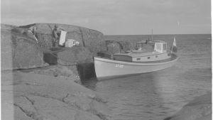 Mustavalkoinen kuva: Vene kiinnitettynä kallioon, kaksi miestä kantaa veneeseen tavaraa.