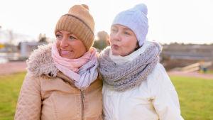 Två leende kvinnor i tofsluva står tätt ihop