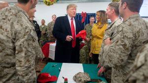 President Donald Trump delade ut kampankepsar under sitt besök på den amerikanska al-Asad-flygbasen i Irak.