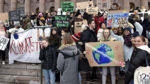 Unga demonstranter på riksdagshusets trappa.