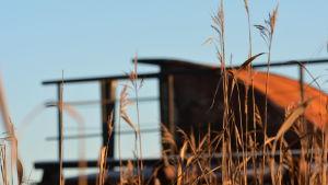 skrotbåt i profil i solnedgången.