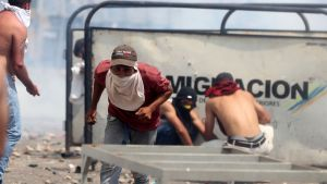 Civila slåss mot Venezuelas polis som inte släpper in transporter via bron  Simón Bolívar  i Cúcuta, Colombia, 23.2.2019
