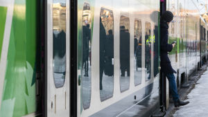 En person håller på att stiga ut ur ett tåg.