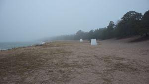 En öde strand med badhytter en dimmig morgon i mars.