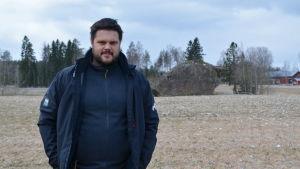 Jesse Mårtenson på en åker med en stor sten i bakgrunden