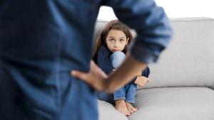 en kvinna står med händerna vid midjan, är vänd mot sin lilla dotter som sitter på soffan och ser rädd ut.