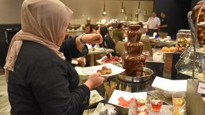 En kvinna tar chokladsås från ett buffébord.