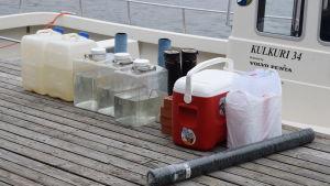 plastdunkar, gummistövlar, matbox med mera på en brygga som väntar på att lastas in i en båt.