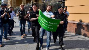 En demonstrant med ett grönt plakat med text på ryska leds bort av två poliser