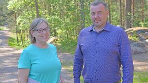 En man och en kvinna står vid en tallskog och ler.