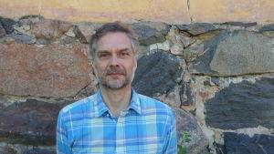 Kenneth Silver står vid en stenvägg i Fiskars iklädd blå kragskjorta.