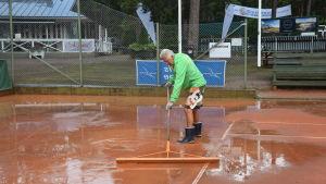 En man torkar upp vatten på en tennisbana. Efter en häftig regnskur.
