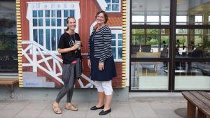Två kvinnor står bredvid varandra och ler. Bakom dem finns en målning och fönster.