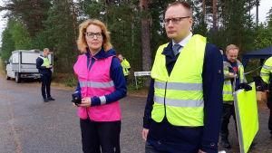 En kvinna med ljusröd väst och en man med gul väst utomhus på en skogsväg.