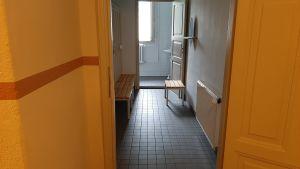 mörk korridor med orange väggar och ljust tvättrum med fönster längre fram