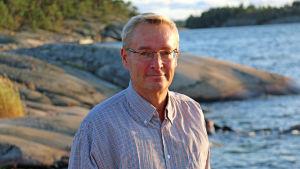 Närbild av en man på en klippig strand.