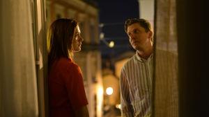 Ett äkta par spelat av Krista Kosonen och Eero Ritala samtalar i mörkret på en hotellbalkong.