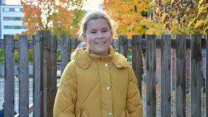 En flicka i en gul jacka ser in i kameran.