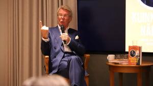 En medelåders man med mikrofon sitter på en stol och hötter med pekfingret.