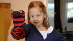 Flicka med röd-svartrandig strumpa på handen.