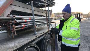 En lastbilschaufför spänner fast gods på sin lastbil.