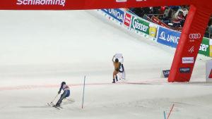Alex Vinatzer rundar sista porten samtidigt som en kvinna i baddräkt korsar mållinjen. Bilden är tagen bakifrån.
