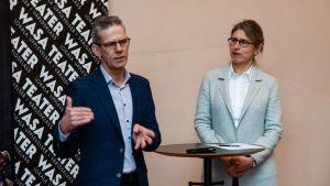 En man och en kvinna på en presskonferens