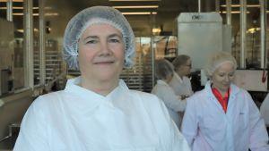 En kvinna med vit skyddsrock och hårskydd