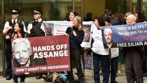 Människor protesterar och håller upp skyltar för Julian Assange i London 14.6.2019.