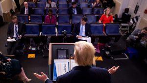 Donald Trump sedd bakifrån i pressrummets talarstol sträcker ut händerna.
