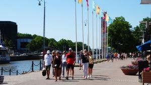Människor promenerar längs med Aura å i sommarsolen.